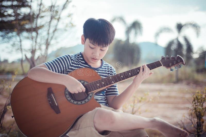 Portret Azjatycki chłopiec gitary gracz ono uśmiecha się przy kamerą zdjęcia stock