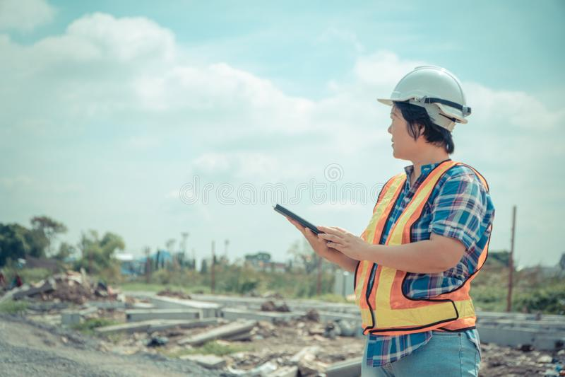 Portret Azjatycki kobiety budowy inżyniera pracownik z hełmem na kierowniczej używa pastylce podczas gdy stojący na budowie Build fotografia royalty free