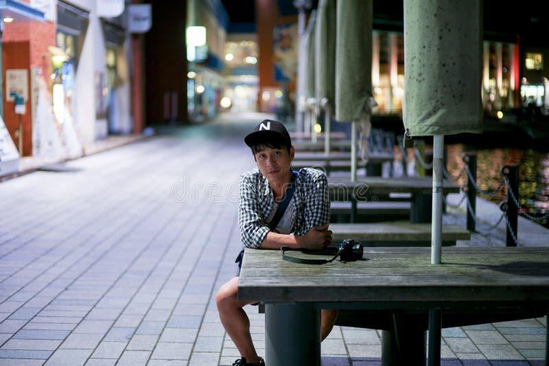 Portret Azjatycki mężczyzna siedzi na drewnianej ławce spojrzeniach przy kamerą i zdjęcie royalty free
