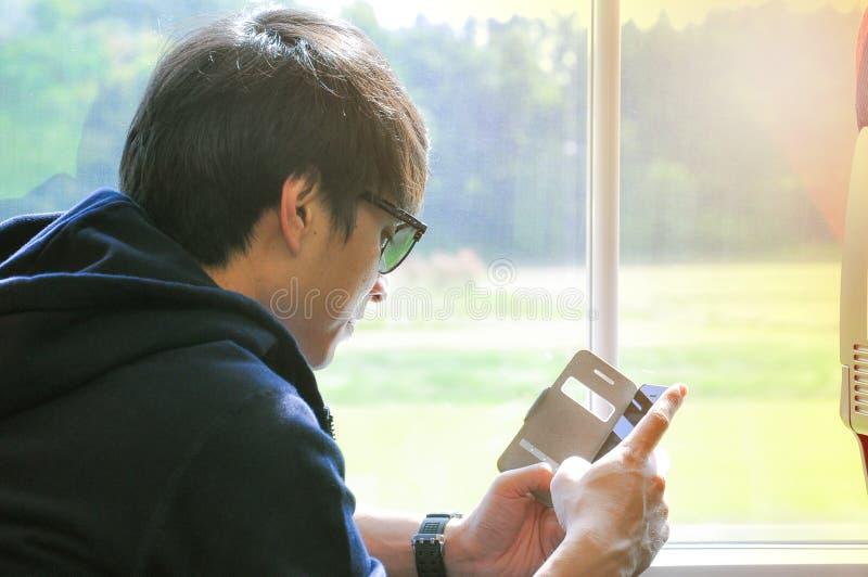 Portret Azjatycki mężczyzny obsiadanie w pociągu i używać wiszącą ozdobę obrazy stock