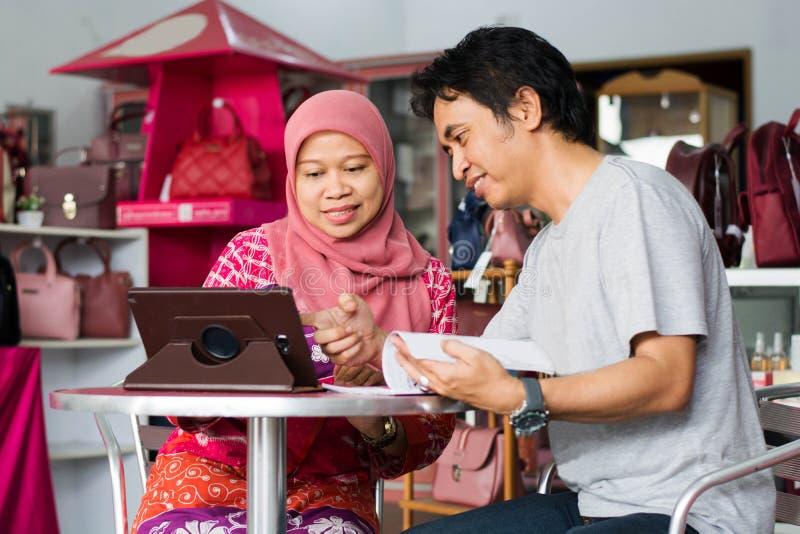 Portret Azjatycki muzułmański wieka średniego mąż i żona dyskutujemy o biznesie w ich sklepie zdjęcie stock