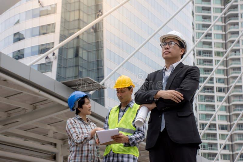 Portret Azjatycki poważny inżynier jest ubranym zbawczego hełma architektów dyskutuje budowa plan zdjęcia stock