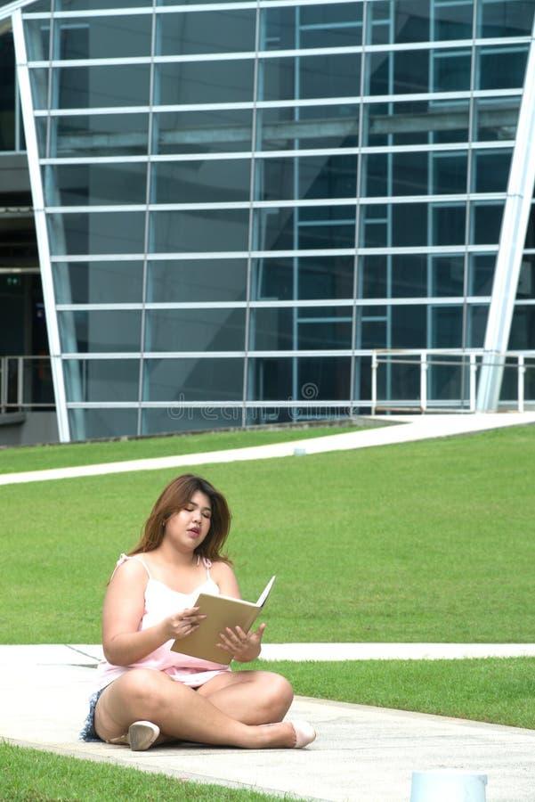 Portret Azjatyckiej ładnej smiley twarzy kobiety gruba poza, mienie i czytanie, książka obraz stock