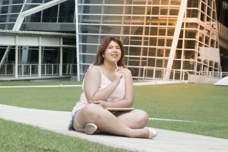 Portret Azjatyckiej ładnej smiley twarzy kobiety gruba poza, mienie i główkowanie, zdjęcia stock