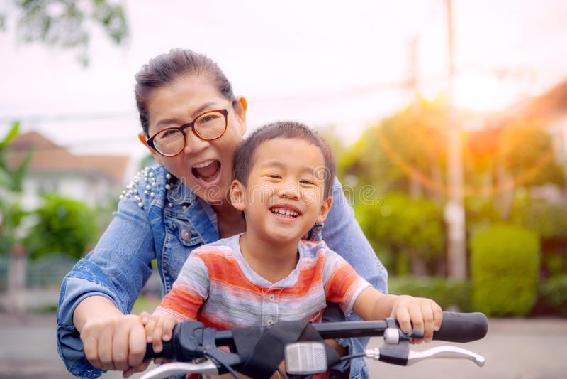 Portret azjatykci dzieci jedzie bicykl z macierzystą uśmiechniętą twarzy szczęścia emocją obraz royalty free