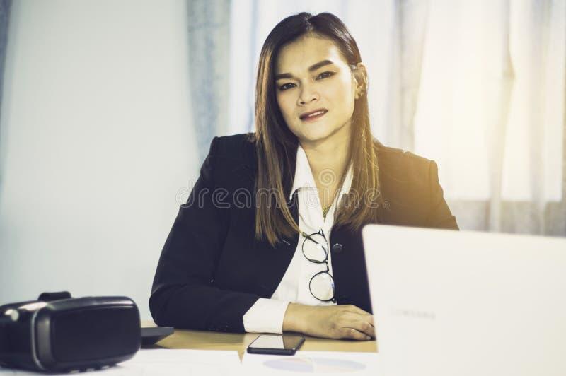Portret azjatykcia biznesowa kobieta z VR i mądrze telefony na stole, z sprzedażami VR słuchawki w świacie początkowy biznes fotografia royalty free
