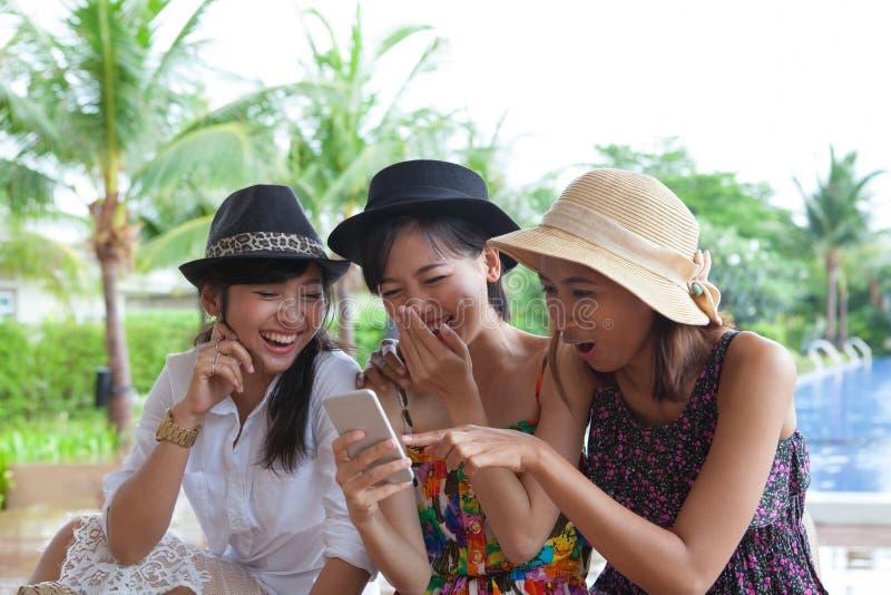 Portret azjatykcia kobieta przyjaciela grupa patrzeje telefon komórkowy i fotografia royalty free