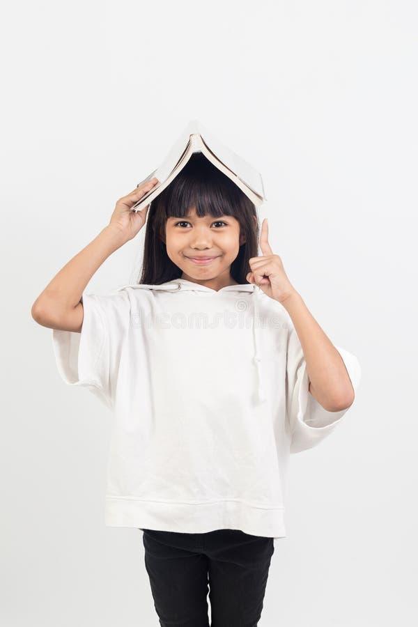 Portret azjatykcia mała dziewczynka stawia książkę na głowie obrazy royalty free