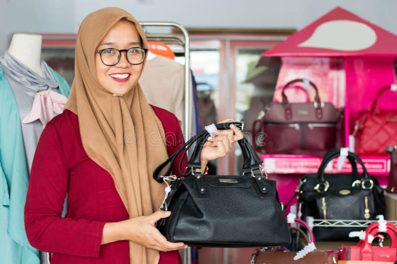 Portret azjatykciego hijab żeński właściciel i kostiumer pozycja z czarną kiesą w jej butik mody sklepie, młody muzułmański - wiz obrazy royalty free