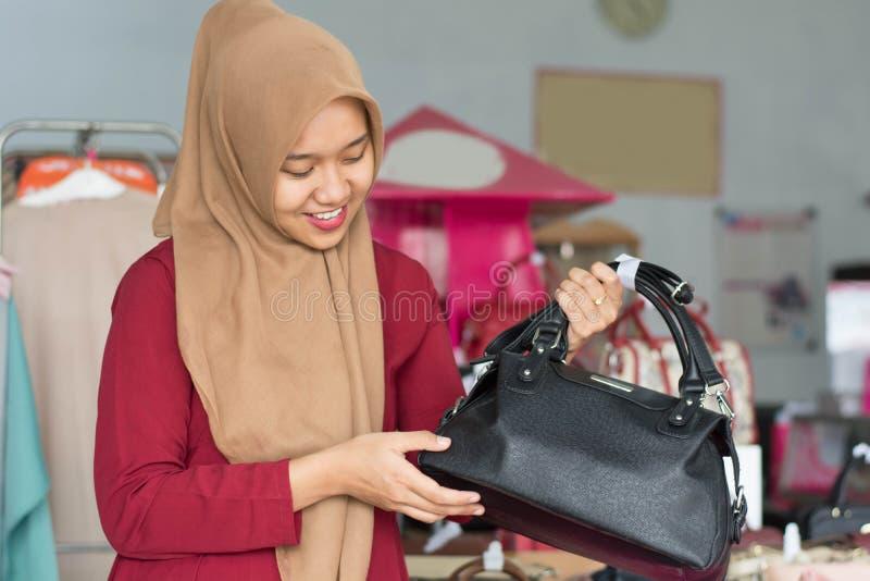 Portret azjatykciego hijab ?e?ski w?a?ciciel i kostiumer pozycja z czarn? kies? w jej butik mody sklepie, m?ody muzu?ma?ski - wiz obraz stock