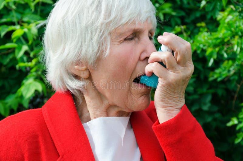 Portret babcia astmę, alergia atak outdoors caucasian babcia używa aerosol, kiść z lekiem, medycyna obrazy stock