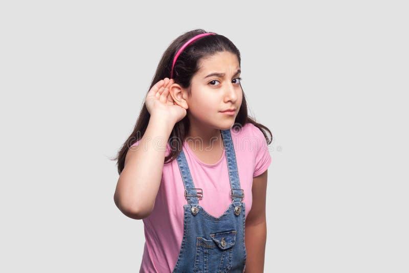 Portret baczna brunetki młoda dziewczyna w koszulce, błękitnych kombinezonach przypadkowej, różowej, i zdjęcie stock