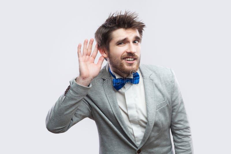 Portret baczny przystojny brodaty mężczyzna w przypadkowym siwieje kostium, błękitną łęku krawata mienia trwanie rękę i próbować  obrazy stock