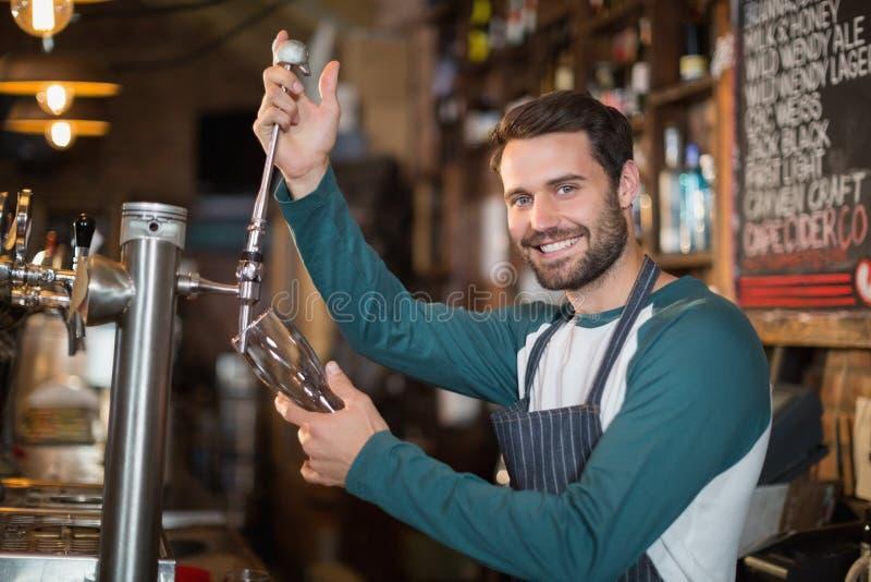 Portret barmanu dolewania piwo od klepnięcia fotografia stock