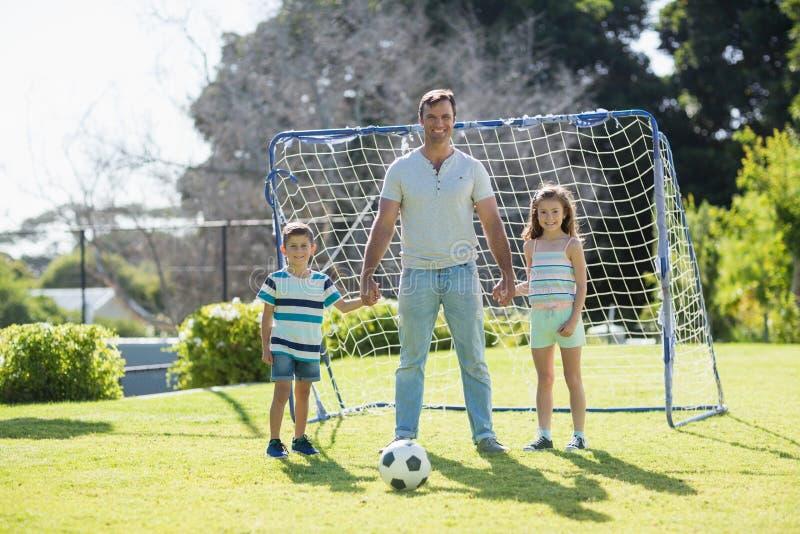 Portret bawić się futbol z jego córką i synem uśmiechnięty ojciec fotografia royalty free