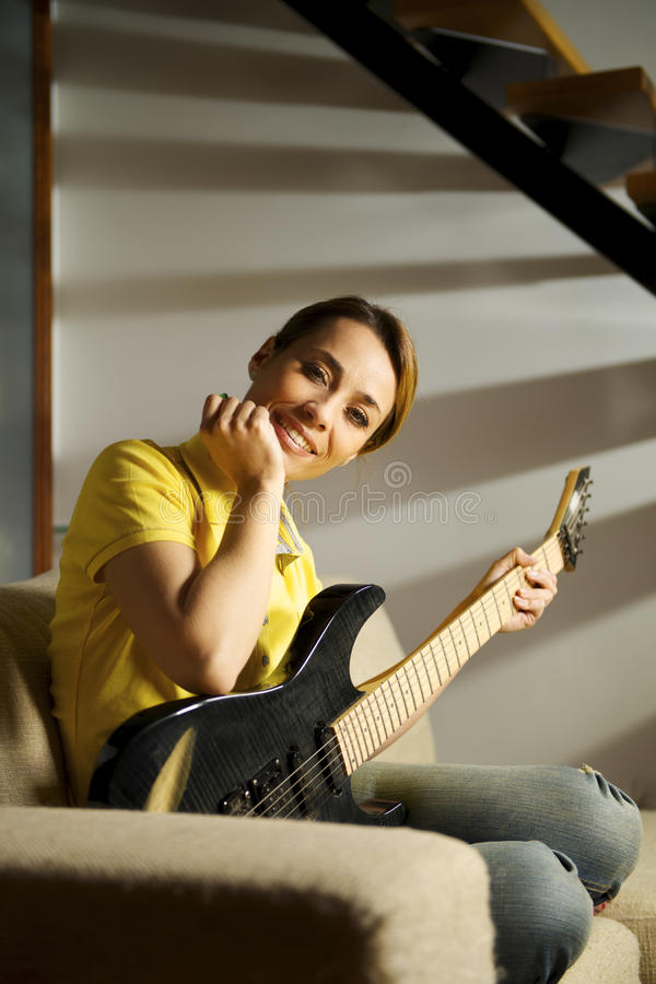 Portret bawić się z gitarą elektryczną w domu kobieta obraz royalty free