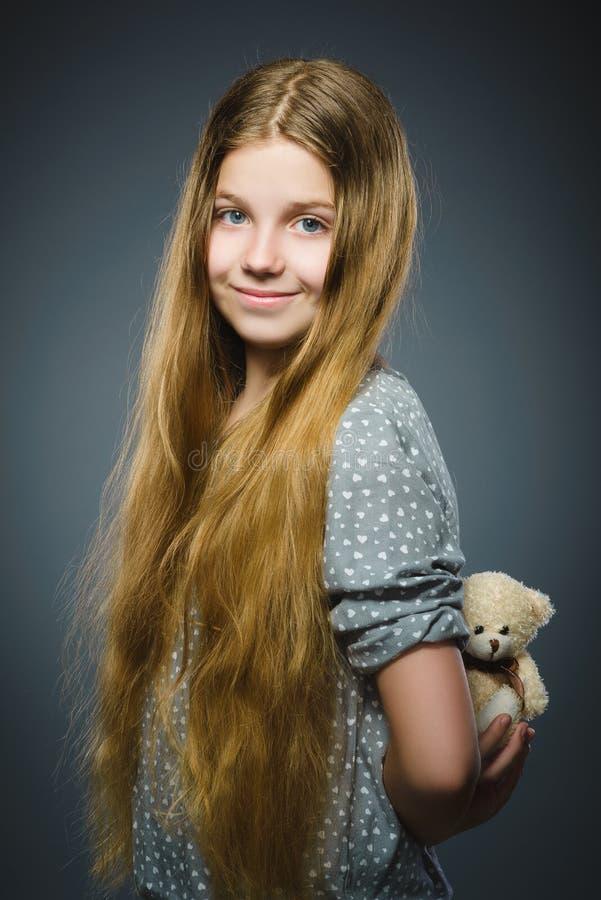 Portret bawić się z misiem odizolowywającym na szarość szczęśliwa dziewczyna fotografia royalty free