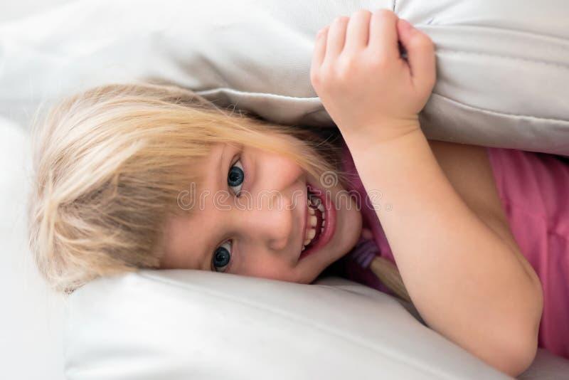 Portret bawić się z poduszkami w łóżku szczęśliwa mała dziewczynka obrazy stock