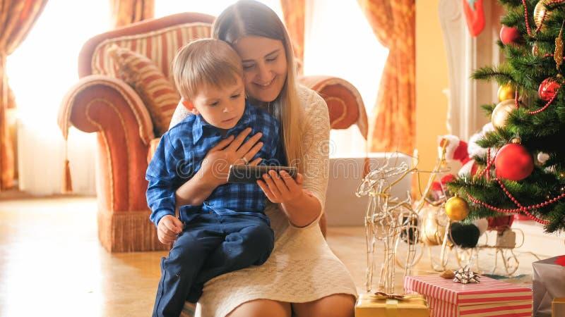 Portret berbeć chłopiec wathcing wideo na telefonie komórkowym z matką przy żywym pokojem dekorował dla bożych narodzeń obraz stock