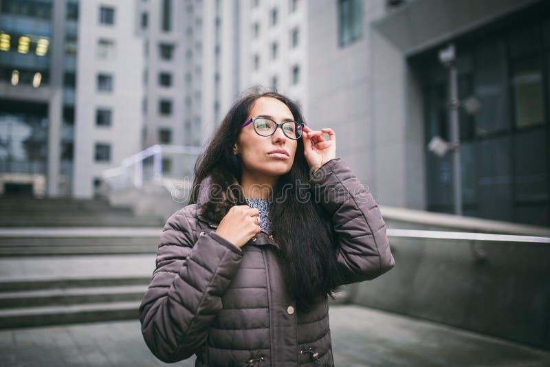 Portret bevindt het mooie jonge bedrijfsvrouwenbrunette zich in jasje en sweater bij de achtergrondbureaubouw, commercieel centru stock fotografie