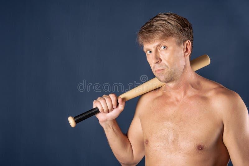 Portret bez koszuli mężczyzna trzyma kij bejsbolowego nad błękitnym tłem zdjęcia royalty free