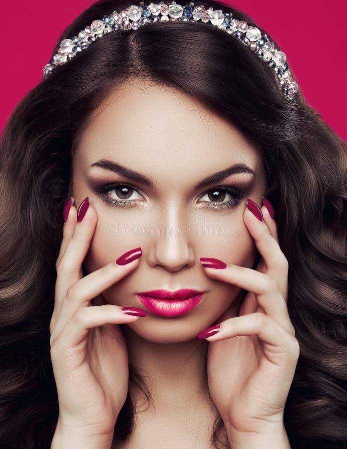 Portret binnen een mooie jonge vrouw met heldere make-up, roze nagellak en roze lippenstift op de mollige lippen royalty-vrije stock afbeeldingen