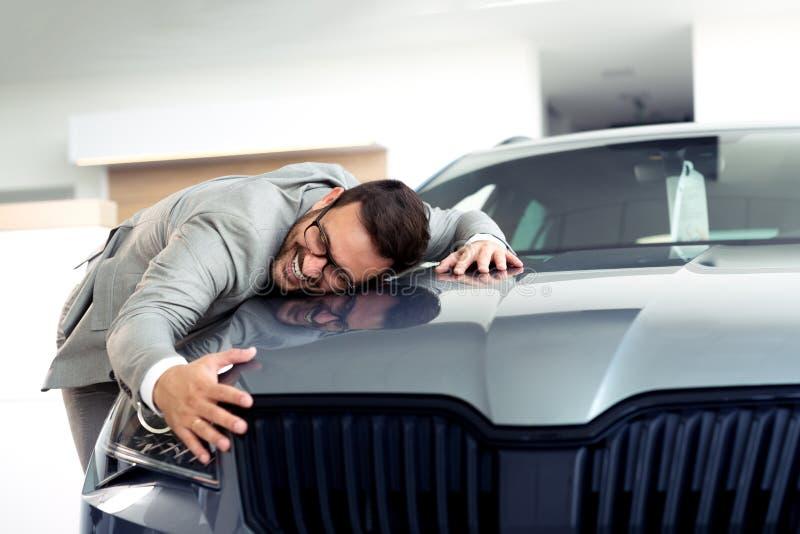 Portret biznesmen ono uśmiecha się joyfully i obejmuje nowego samochód przy przedstawicielstwo handlowe sala wystawową obraz royalty free