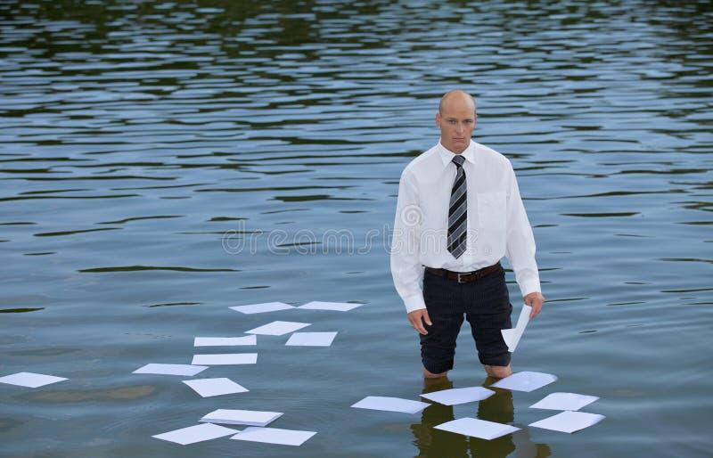 Portret biznesmen pozycja w jeziorze z papierami unosi się na wodzie zdjęcie stock