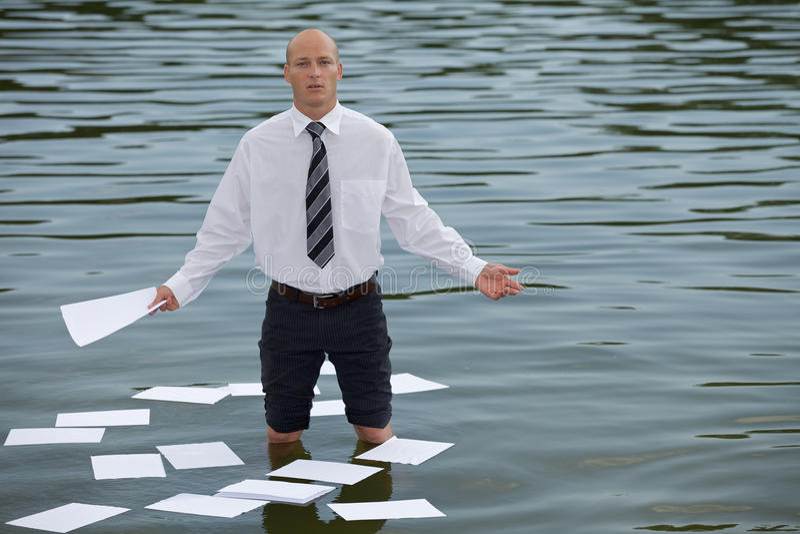 Portret biznesmen pozycja w jeziorze z papierami unosi się na wodzie zdjęcie royalty free
