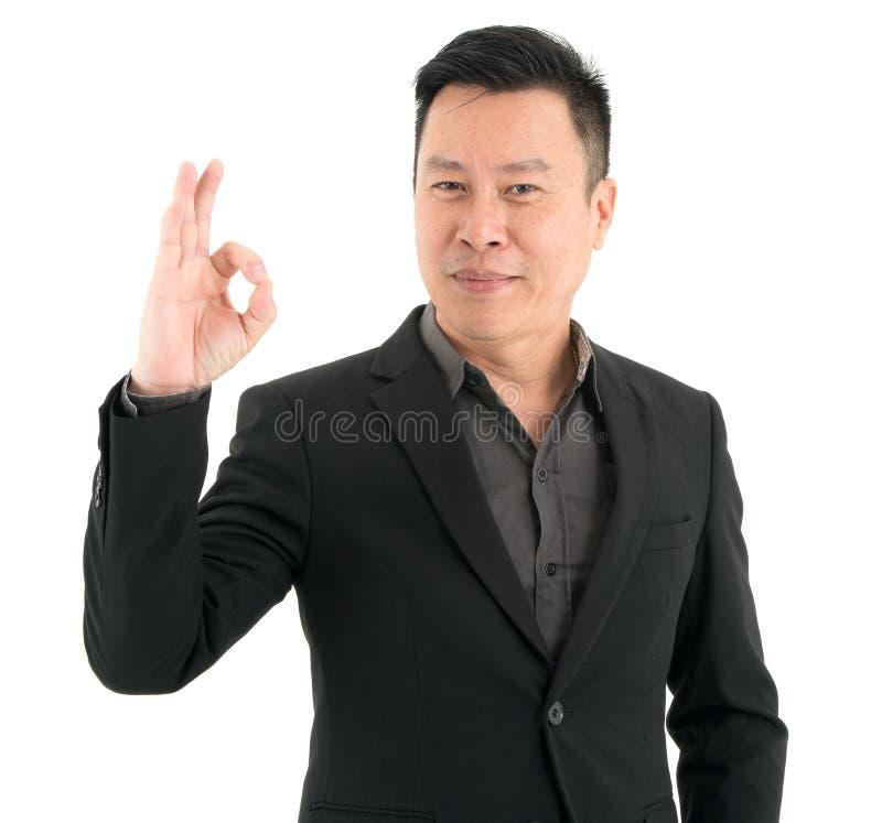 Portret biznesmen teraźniejszości zaufanie pokazuje OK palce, odosobniony na białym tle obraz stock