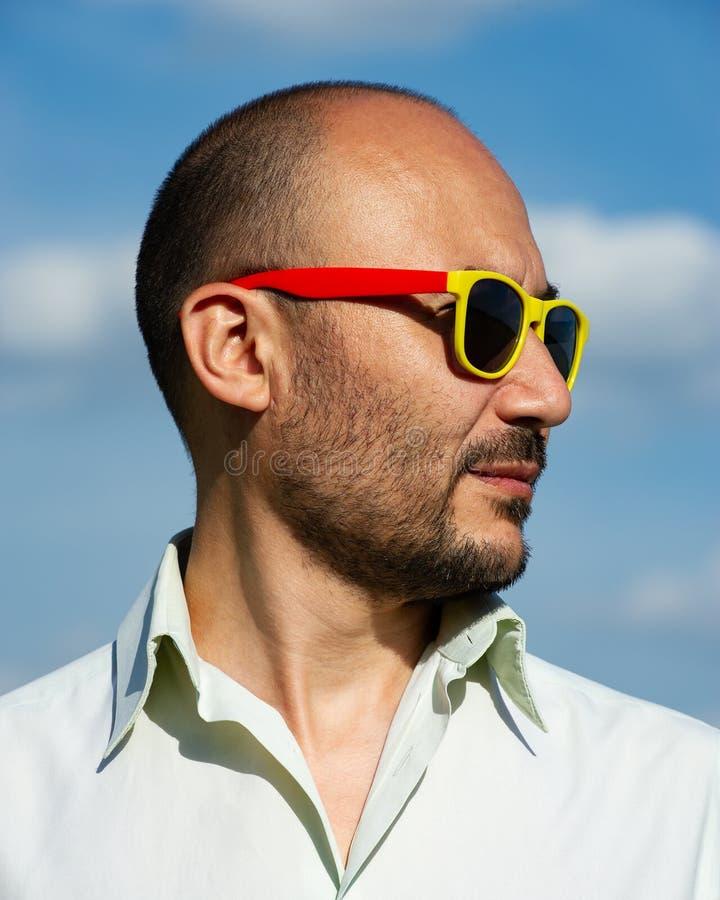 Portret biznesmen w nowożytnych okularach przeciwsłonecznych przeciw błękitnemu sk obraz stock