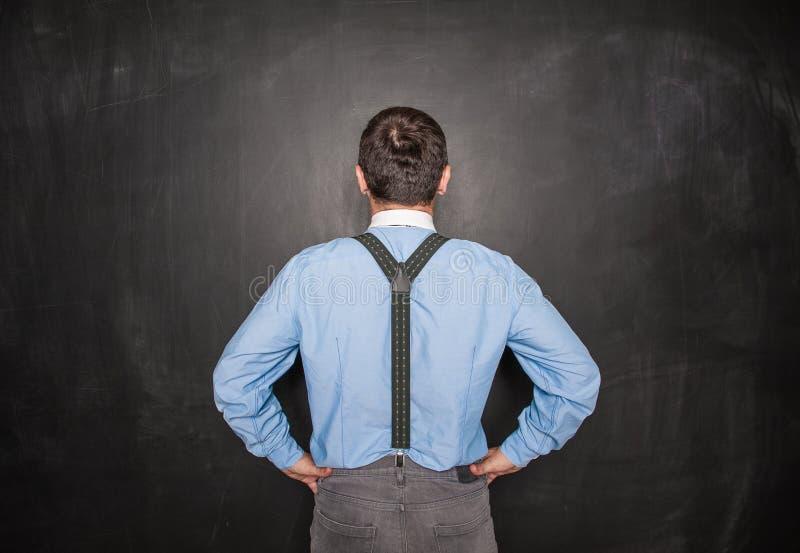 Portret biznesmena lub nauczyciela tylny widok na blackboard fotografia stock