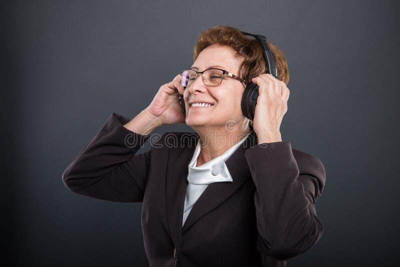 Portret biznesowa starsza dama cieszy się słuchać hełmofon obraz stock
