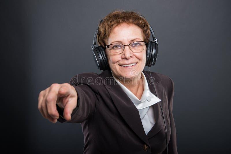 Portret biznesowa starsza dama słucha hełmofony pointin obraz stock