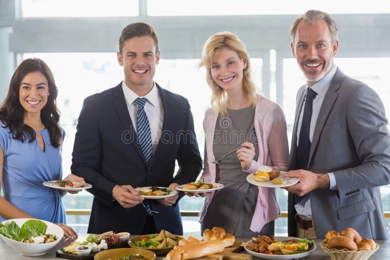 Portret biznesowi koledzy ono słuzyć przy bufeta lunchem zdjęcie stock