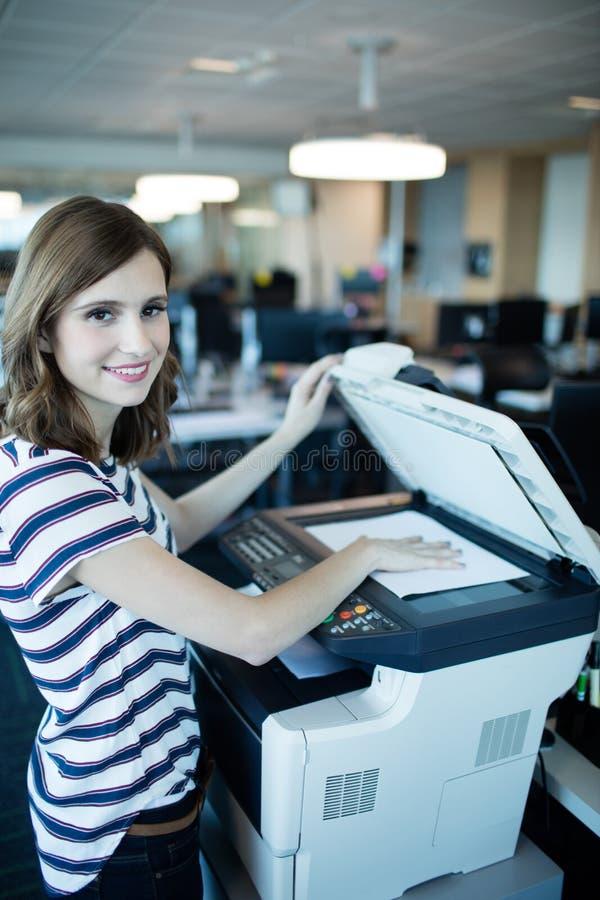 Portret bizneswoman używa odbitkową maszynę w biurze obraz royalty free