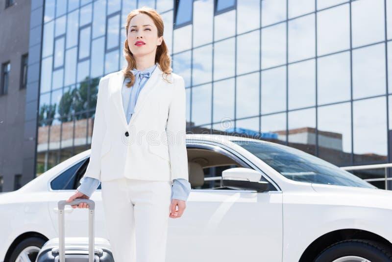 portret bizneswoman w białym kostiumu z walizki pozycją przy samochodem fotografia stock