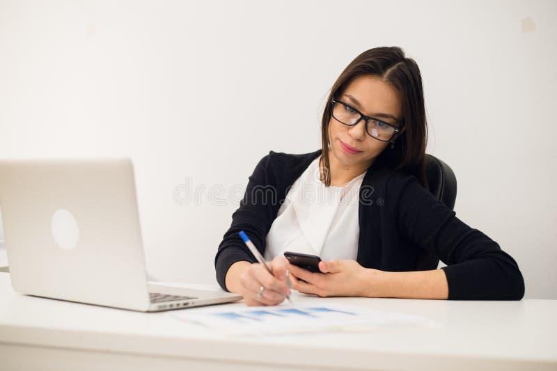 Portret bizneswoman z laptopem pisze na dokumencie przy jej biurem zdjęcia royalty free