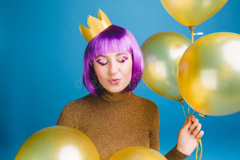 Portret blije jonge vrouw met besnoeiings purper haar die pret op blauwe achtergrond hebben Gouden ballons, die een kus verzenden stock afbeelding
