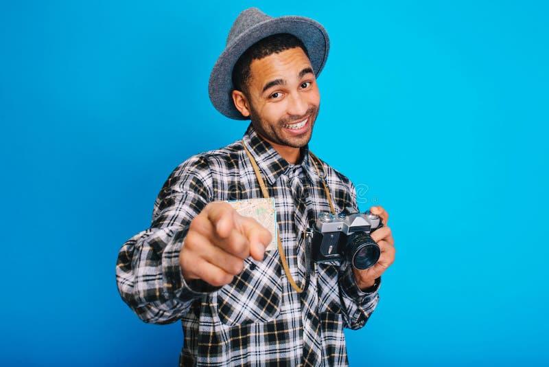 Portret blije modieuze kerel met kaart en camera die op blauwe achtergrond glimlachen Toerist, die pret, vrolijk reizen hebben, stock foto's