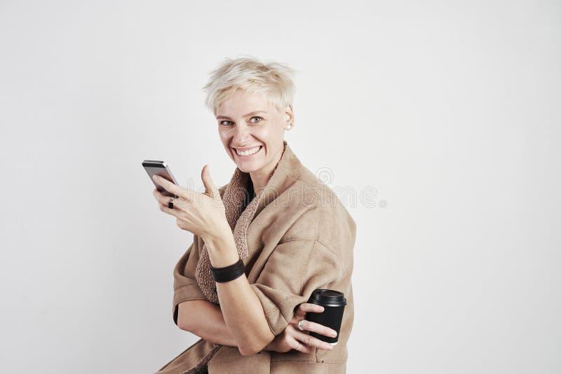 Portret blond caucasian kobiety uśmiechnięty roześmiany emoticon pije takeaway kawę, używać smartphone na białym tle obraz royalty free