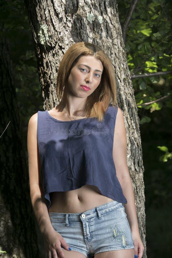 Portret blond kobieta opiera na drzewie zdjęcie stock