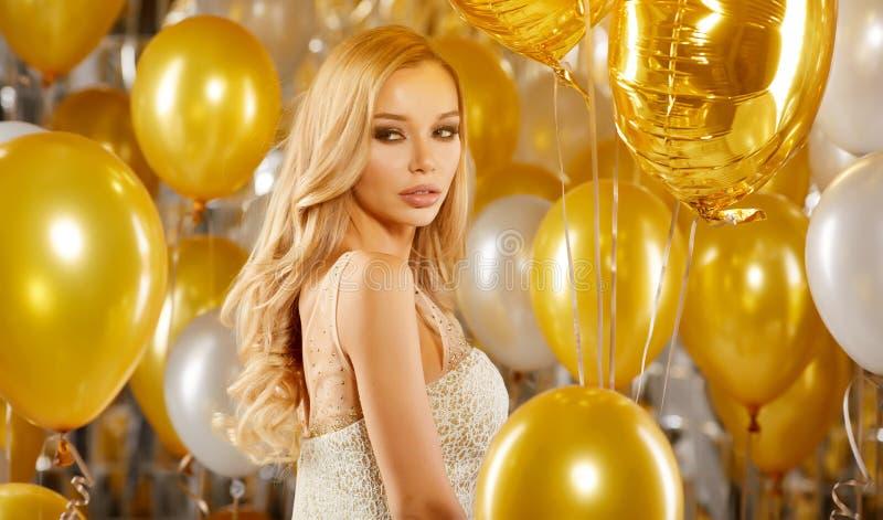 Portret blond młoda kobieta między złotymi balonami i faborkiem zdjęcia royalty free