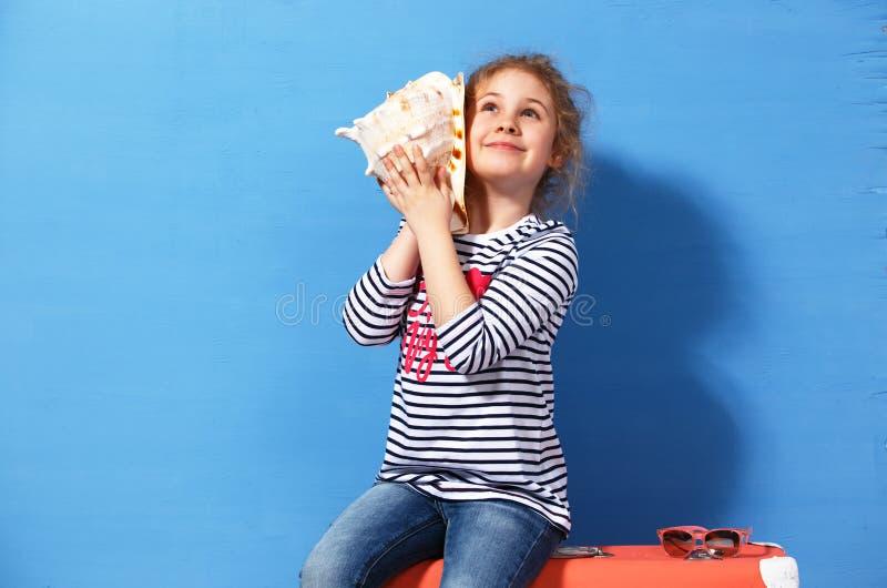 Portret blondynki dziecka dziewczyna słucha seashell przy błękitną ścianą Wakacje pojęcie fotografia stock