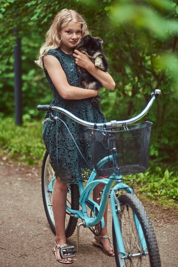 Portret blondynki dziewczyna w przypadkowej sukni troszkę, chwyta spitz śliczny pies w parku, obraz stock