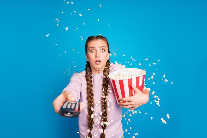 Portret boi się młodszej dziewczyny z warkoczykami oglądać telewizję z popcornem zobaczyć horror series chce przełącznik obraz stock