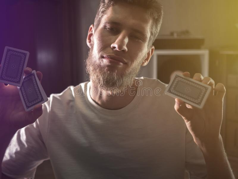 Portret brodaci młodego człowieka mienia karta do gry robić sztuczce w ciemnym tle obraz stock