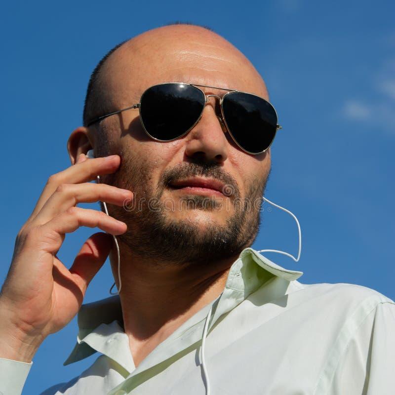 Portret brodaty strażnik jest ubranym okulary przeciwsłonecznych z hełmofonami, zdjęcia royalty free