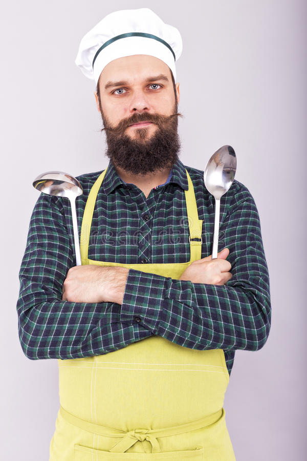 Portret brodaty szef kuchni trzyma dwa dużego kuchennego naczynia, chłopaczyna obraz royalty free