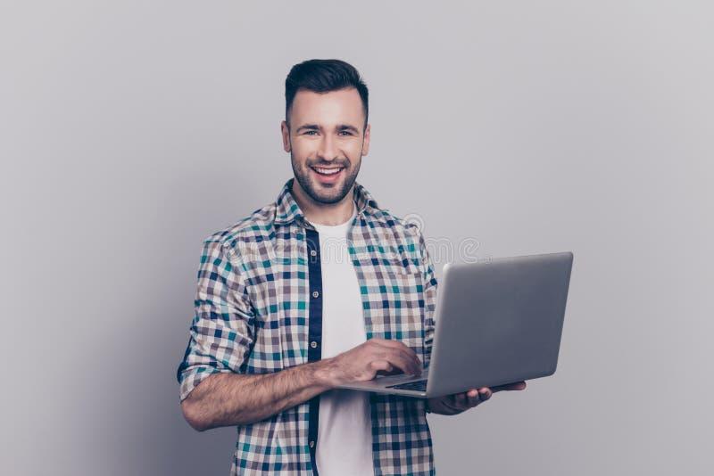 Portret brodaty uśmiechnięty brunet faceta mienia laptop, patrzeje obraz stock